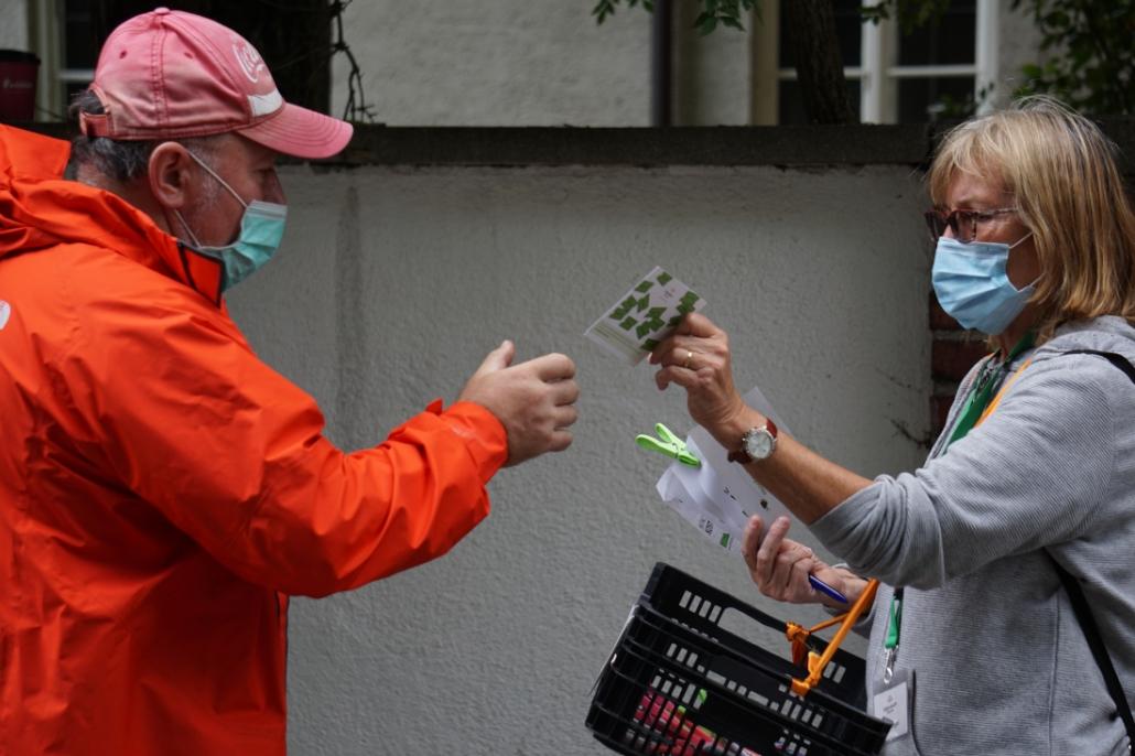 Eine Ehrenamtliche gibt einem Tafelgast einen Flyer