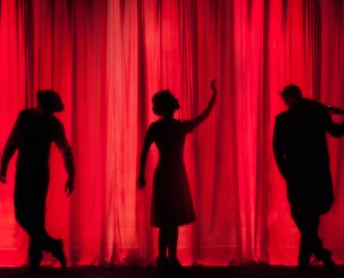 Drei Figuren vor einem Vorhang