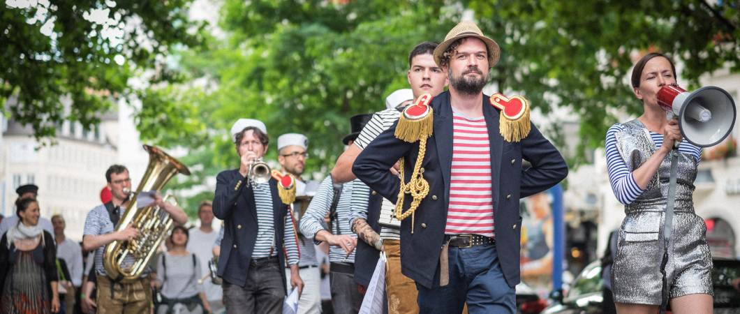 Bunt gekleidete Musiker:innen bei einer Prozession