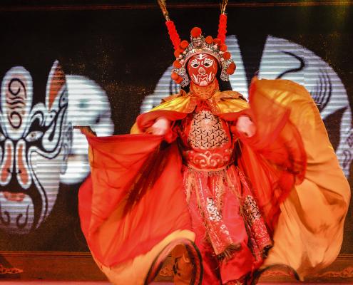 Schauspieler der chinesischen Oper in leuchtend orangem Kostüm