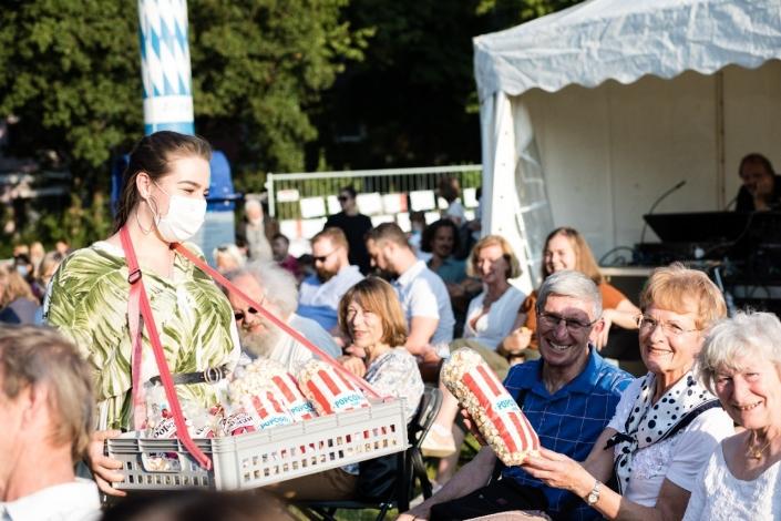 Eine junge Frau verkauft Popcorn an das Publikum