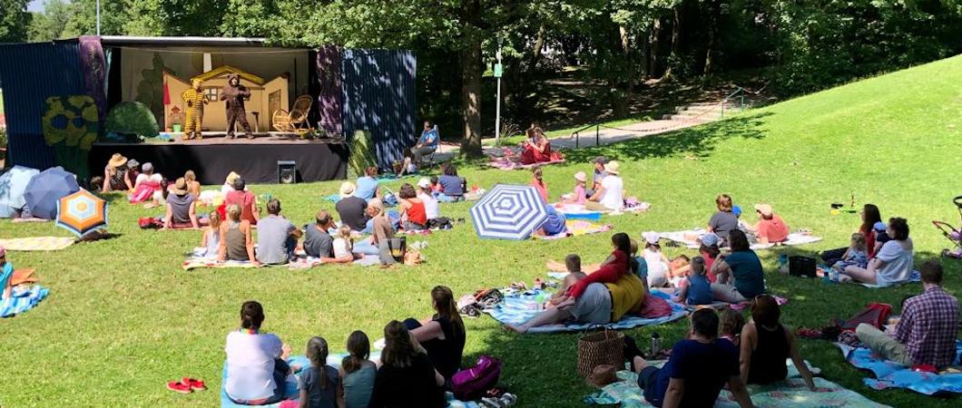 Familien sitzen auf einer Wiese und sehen ein Theaterstück an