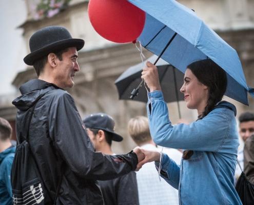 Ein Mann mit Hut gibt einer Frau, die einen roten Luftballon und einen blauen Regenschirm in der Hand hält, die Hand.