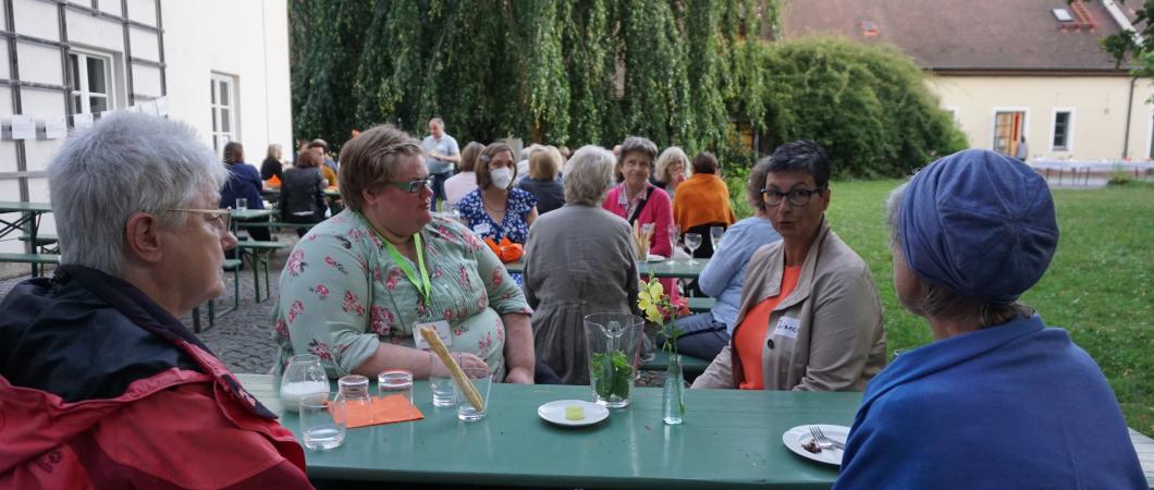 Menschen sitzen im Garten der Mohr-Villa und unterhalten sich