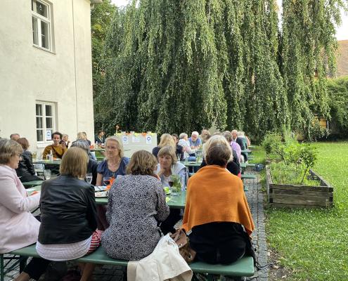Menschen sitzen im Garten der Mohr-Villa auf Bierbänken und unterhalten sich