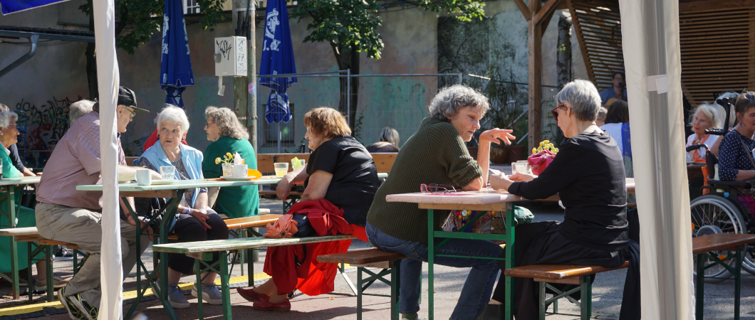 Menschen sitzen an Bierbänken und unterhalten sich