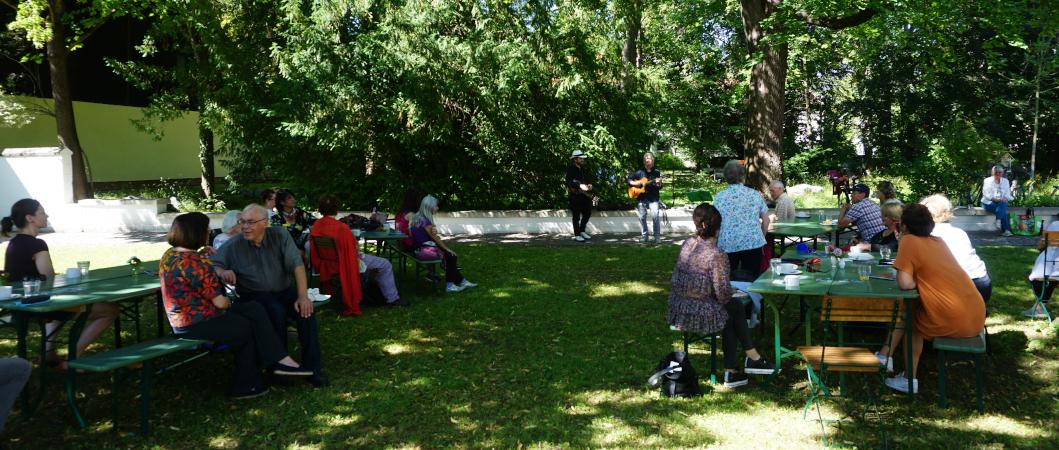 Menschen sitzen im Garten der Mohr-VIlla, unterhalten sich und hören ein kleines Konzert